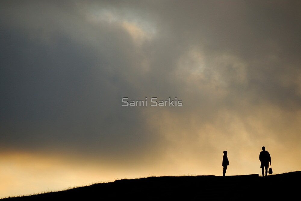 Silhouettes of two people standing on horizon, dusk by Sami Sarkis