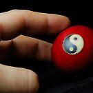 Hand on meditation ball with Yin Yang symbol by Sami Sarkis