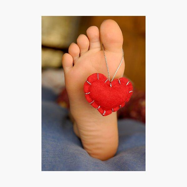 Valentine heart hanging on girl's barefeet Photographic Print
