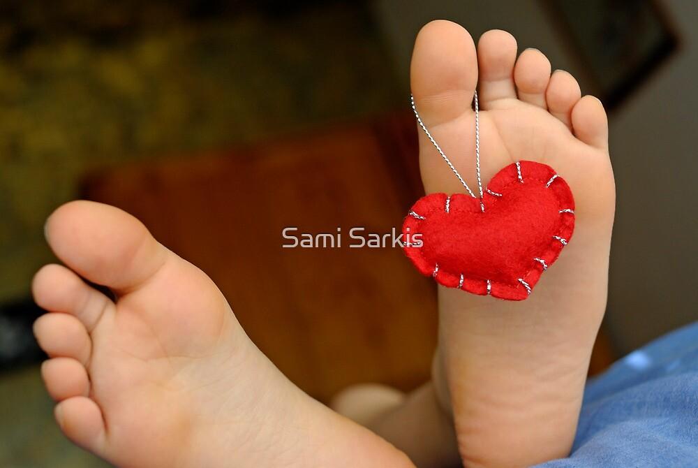 Valentine heart hanging on girl's (6-7) barefeet by Sami Sarkis