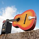 Damaged guitar and railway lamp on a wooden beam by wildrain