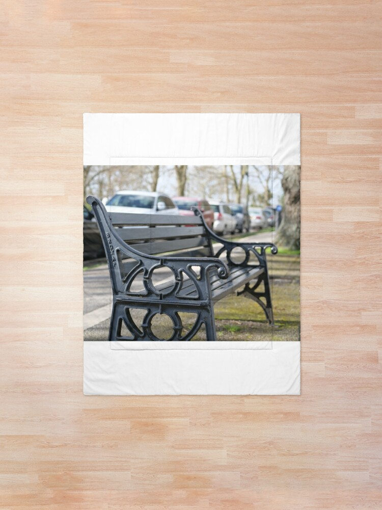 Alternate view of Bench for people to sit along the Thames river embankment in Windsor, Berkshire, England, UK Comforter