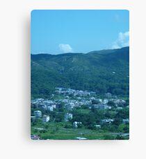 Mountains surrounding a little village Canvas Print