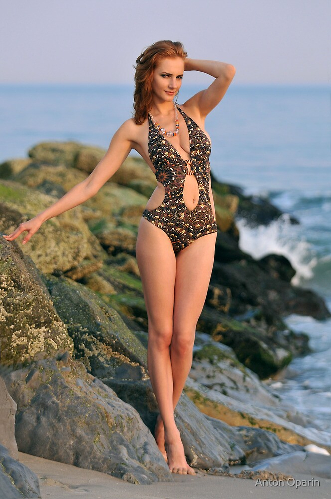 Young redhead girl on the beach standing pretty in designers swimsuit at rocky jetty by Anton Oparin