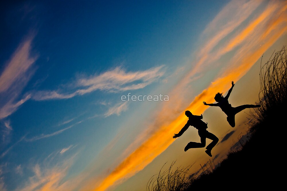 Happy couple jumping in the sunset by efecreata