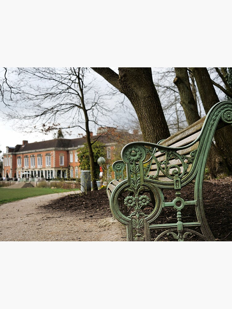 A bench in the park with a background of  South Hill Park Arts Centre, Bracknell, England, UK by santoshputhran