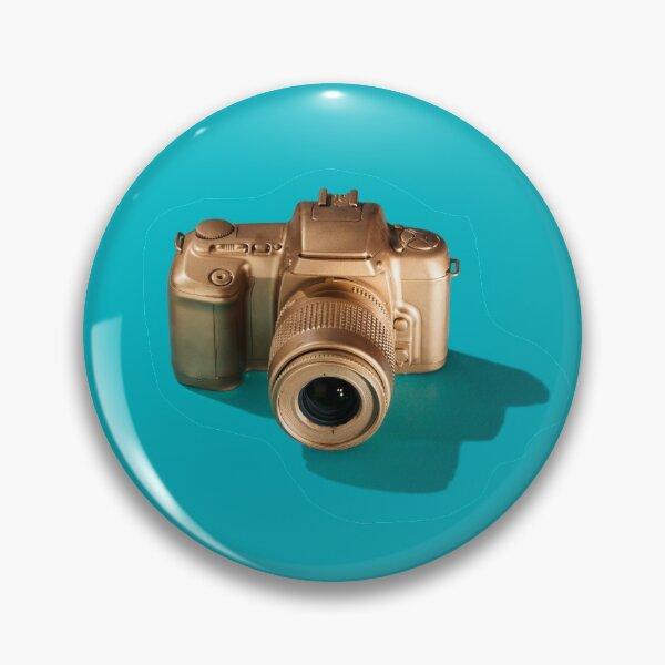 Golden SLR Camera on Cyan Pin