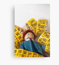 Doll resting on measuring tape Metal Print
