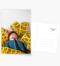 Doll resting on measuring tape Postcards