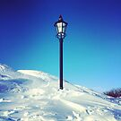 Old Lamp Post in Snow with Blue Sky by Nadine Staaf