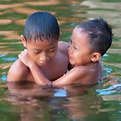Two boys swimming in the sacred lake at sunset in Candidasa, Bali, Indonesia by Michael Brewer