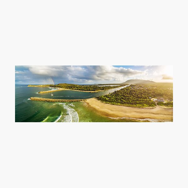 Scenic aerial panorama of ocean coastline, rainbow, and boat at sunset Photographic Print