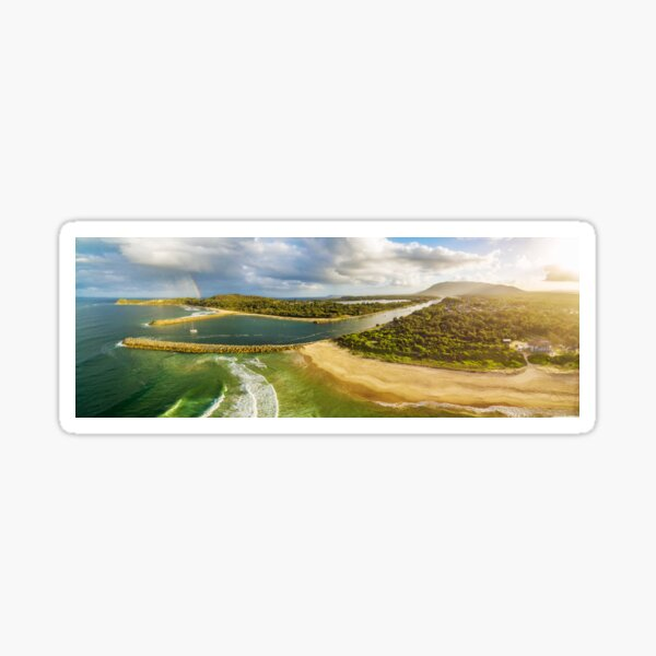 Scenic aerial panorama of ocean coastline, rainbow, and boat at sunset Sticker