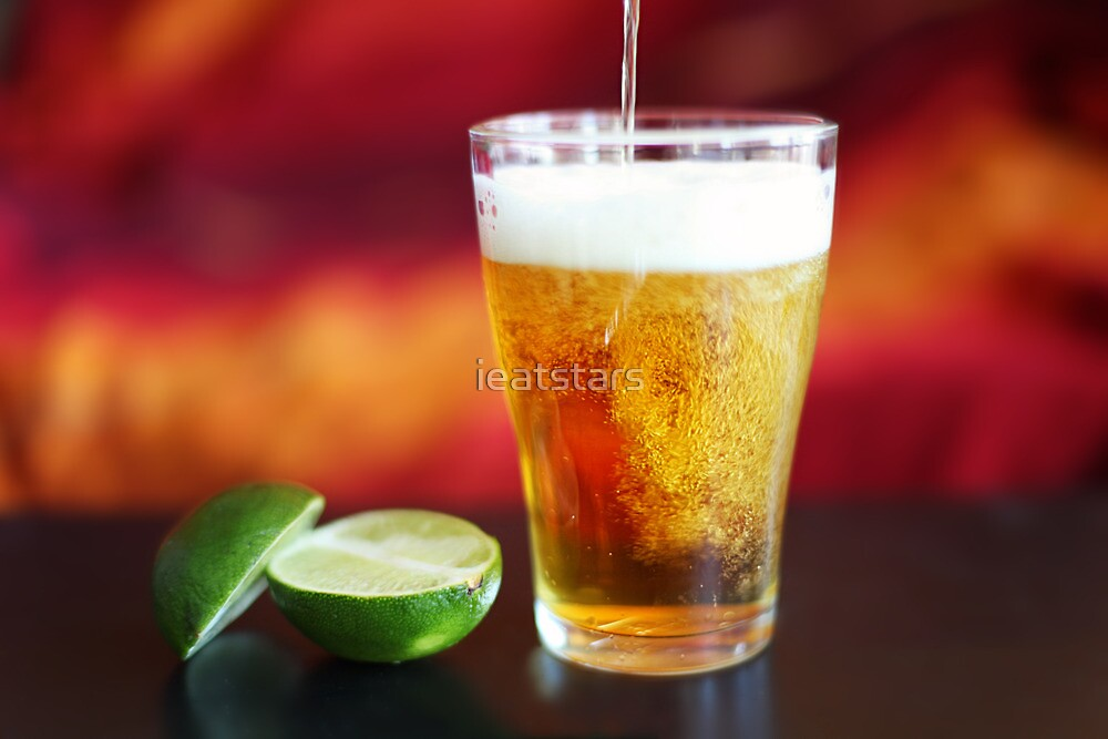 Beer being poured into glass with lime by ieatstars