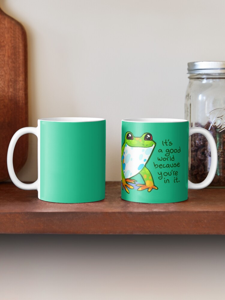 """Alternate view of """"It's a good world because you're in it"""" Frog Mug"""