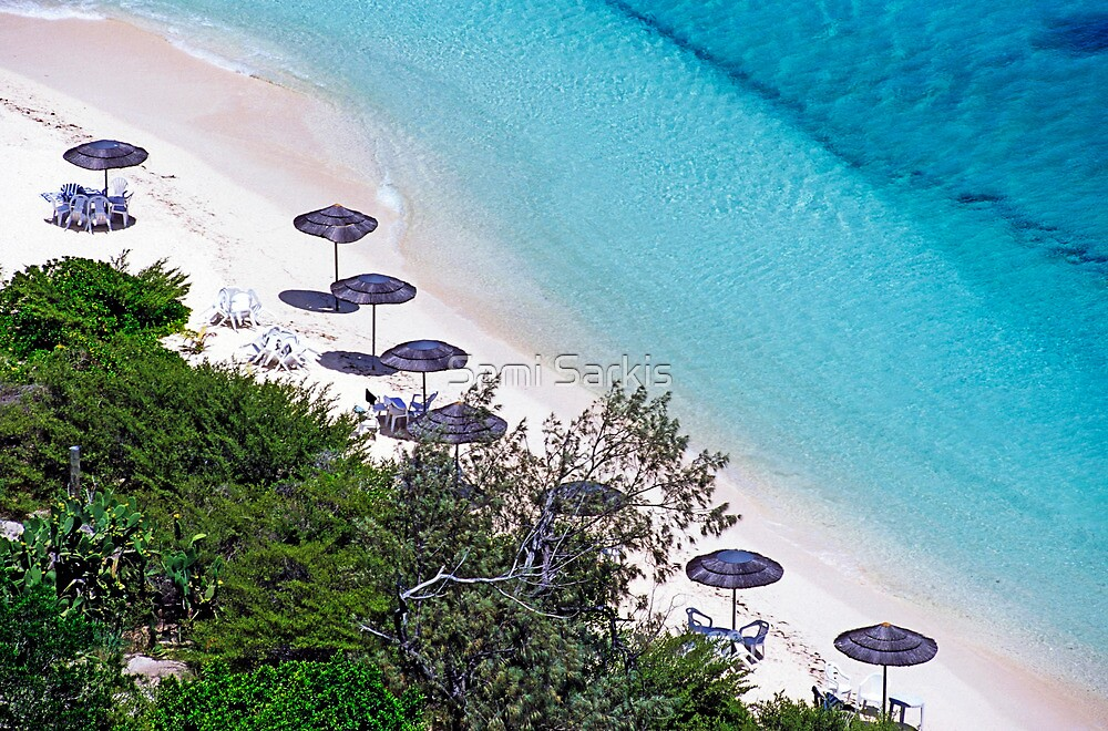 Sun umbrellas dotted along the white sand beach by Sami Sarkis