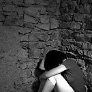 Depressed woman sitting with head in hands in a room corner  by Sami Sarkis