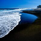 The black sand of Etang Salé beach by Rémi Bridot
