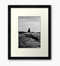 A lady sitting on a rock Framed Print