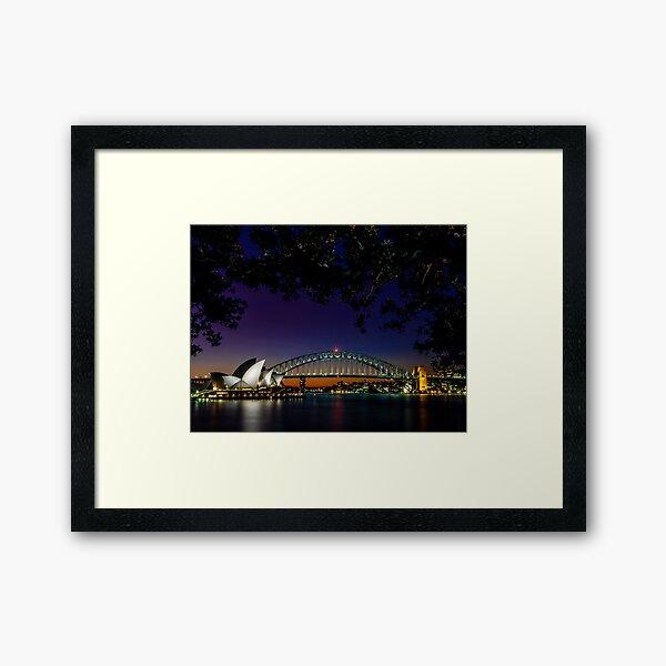 Sydney Harbour Bridge and Sydney Opera House at night framed by trees Framed Art Print