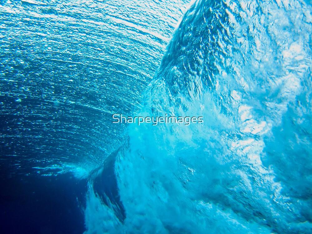 Underwater view of breaking wave in blue ocean by Sharpeyeimages