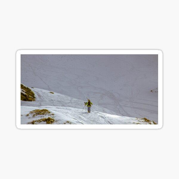 Skier walking uphill on snow mountain Sticker