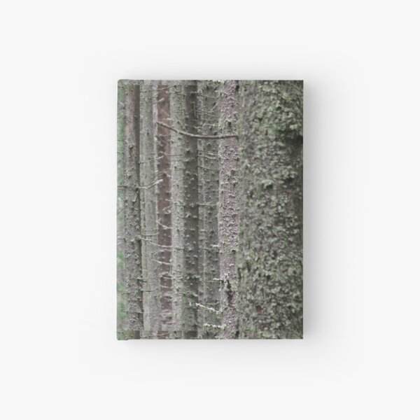 Pine tree trunks covered in moss Hardcover Journal