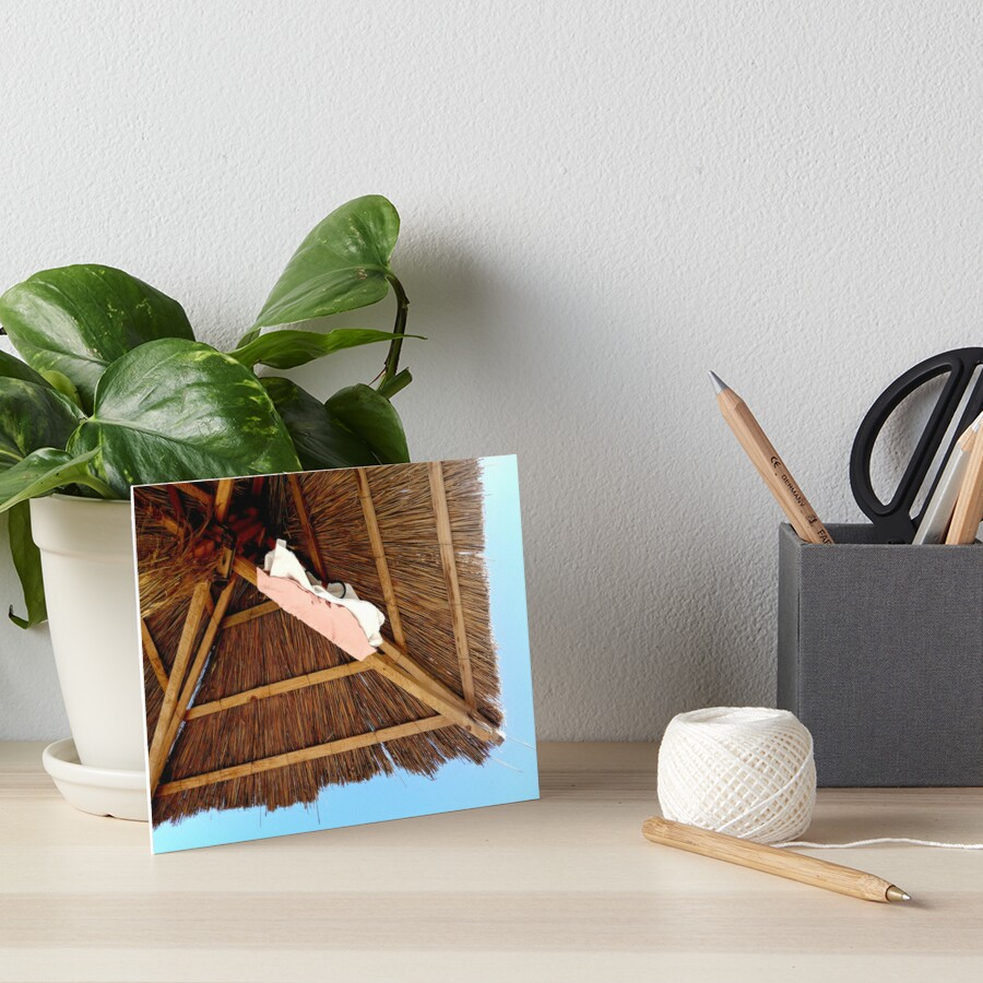 Straw beach umbrella, seen from below, two pink and white t-shirts hanging from it, cloudless blue sky Art Board Print