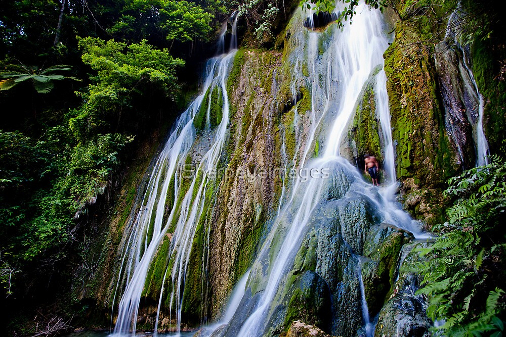 Man standing in waterfall, Vanuatu, South Pacific Ocean by Sharpeyeimages