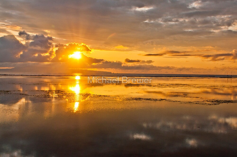 Rising sun, reflections and clouds at dawn seen in Sanur Beach in Bali, Indonesia by Michael Brewer