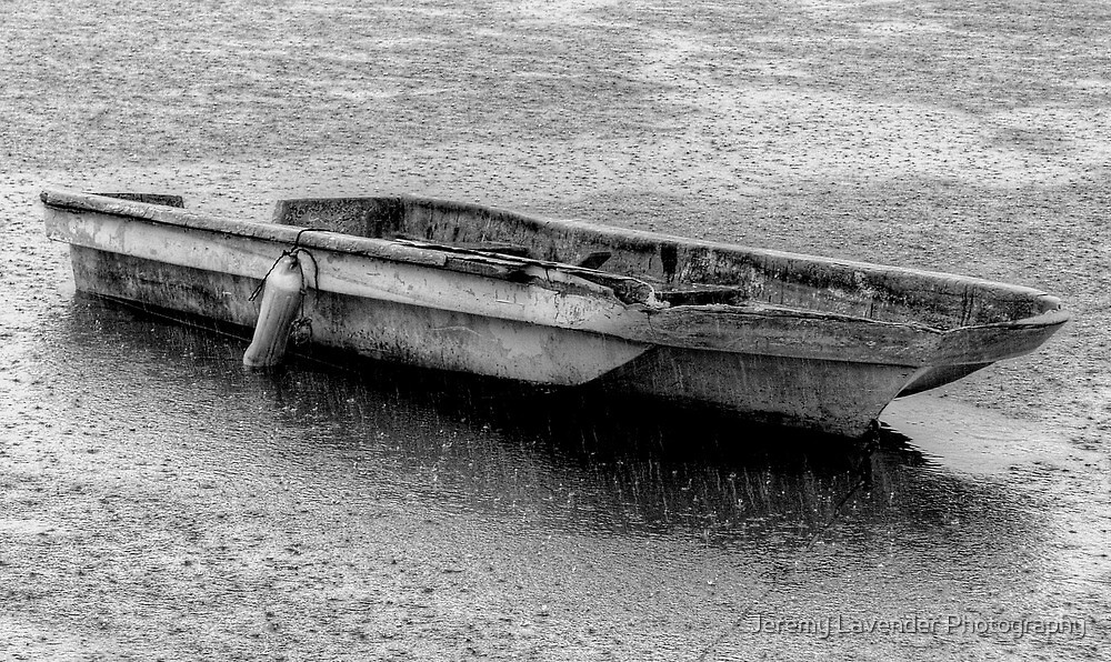 Small boat under a heavy rain in Nassau Harbour, The Bahamas by Jeremy Lavender Photography