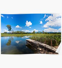 Wetland pond and wooden bridge in a clear sky Poster