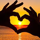 Silhouette hand in heart shape and sunrise over the ocean by gianliguori