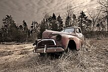 Abandoned rusted old truck in field by Jim Cumming