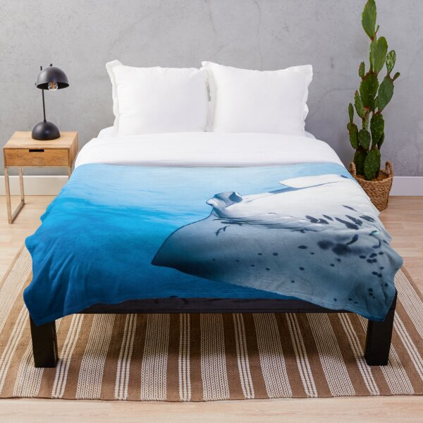 Cute Manta ray swimming in the blue ocean Throw Blanket