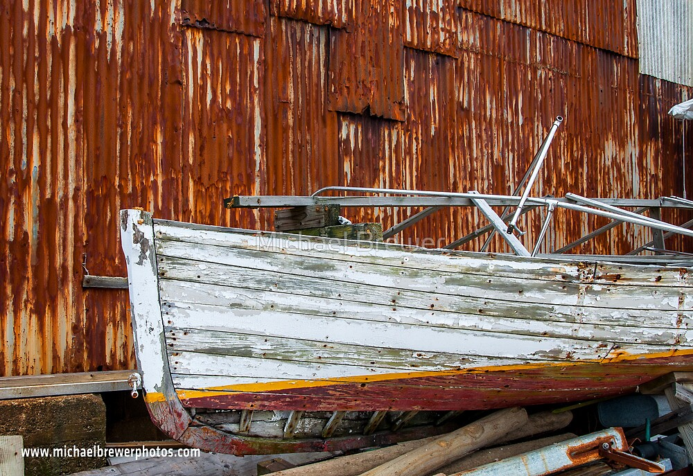 Rotting Boat against Rusty Building by Michael Brewer