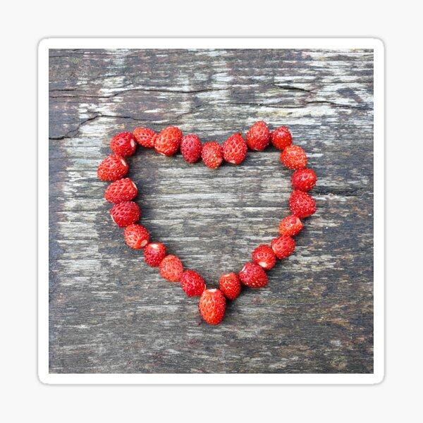 Wild strawberries in shape of heart on wood Sticker