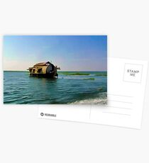 A houseboat moving placidly through a coastal lagoon in Alleppey Postcards