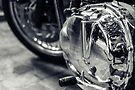 Motorbike engine with reflections of a paved street by OlivierImages