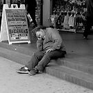 Hobo sleeping on steps on Broadway St. in downtown Los Angeles. by philw