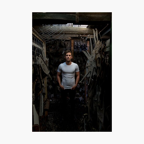 Fit young man standing in a dark industrial workshop Photographic Print