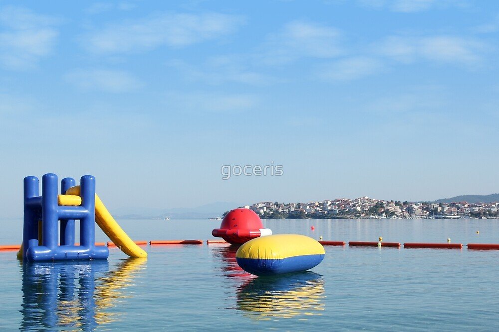 beach toys and equipment floating on sea by goceris