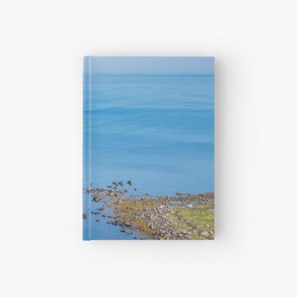 Coastlines frame the blue sea Hardcover Journal