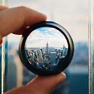 Man holding a lens over Manhattan by Giorgio Fochesato