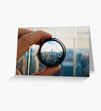 Man holding a lens over Manhattan Greeting Card