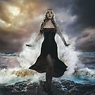the forces of nature, blonde woman on the rocks with the sea raging and powerful by Fernando Cortés