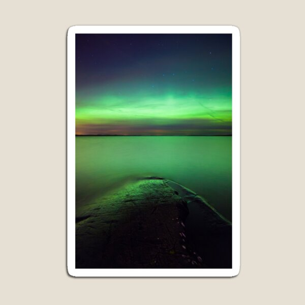 Northern lights glow over lake Magnet