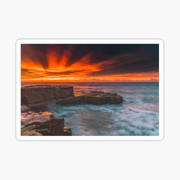 Vibrant red sunrise sky over the sea from rock platform Sticker
