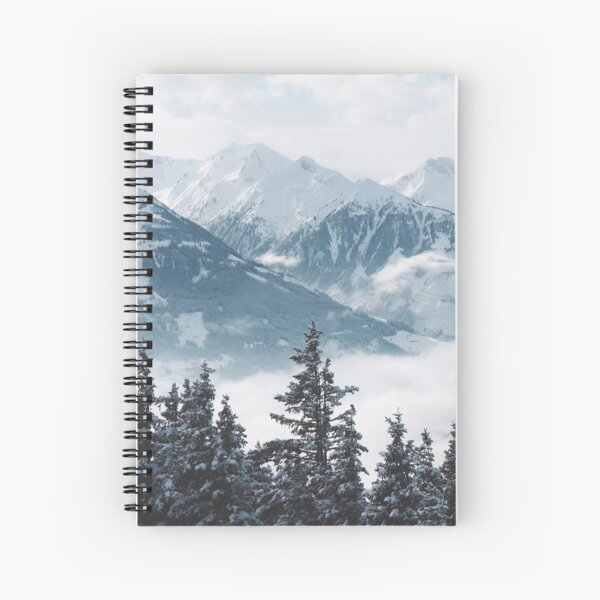 Beautiful shot of mountains and trees covered in snow and fog Spiral Notebook
