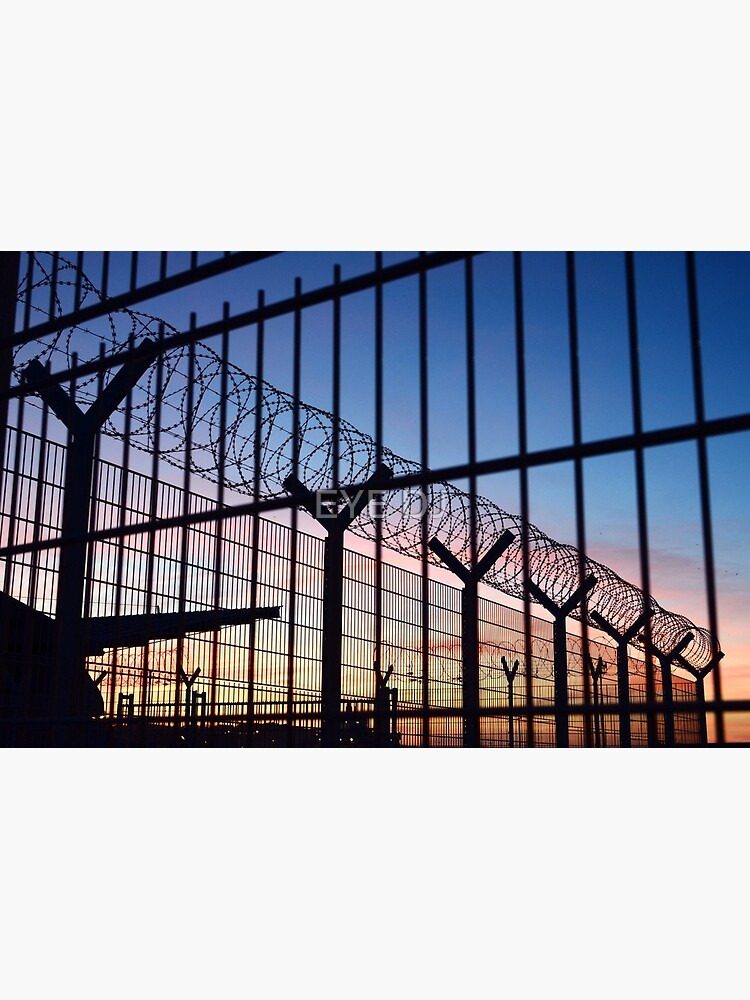 View through a barbed wire fence with beautiful colourful sunset sky in Dieppe France by iDJPhotography